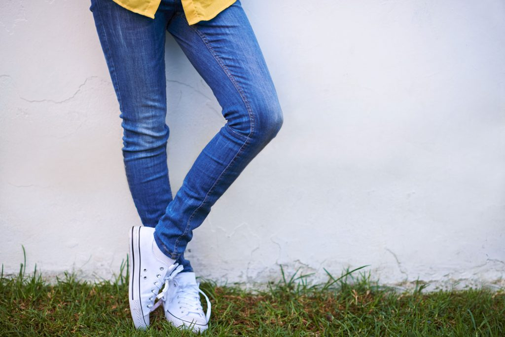A woman wearing white sneakers and skinny jeans