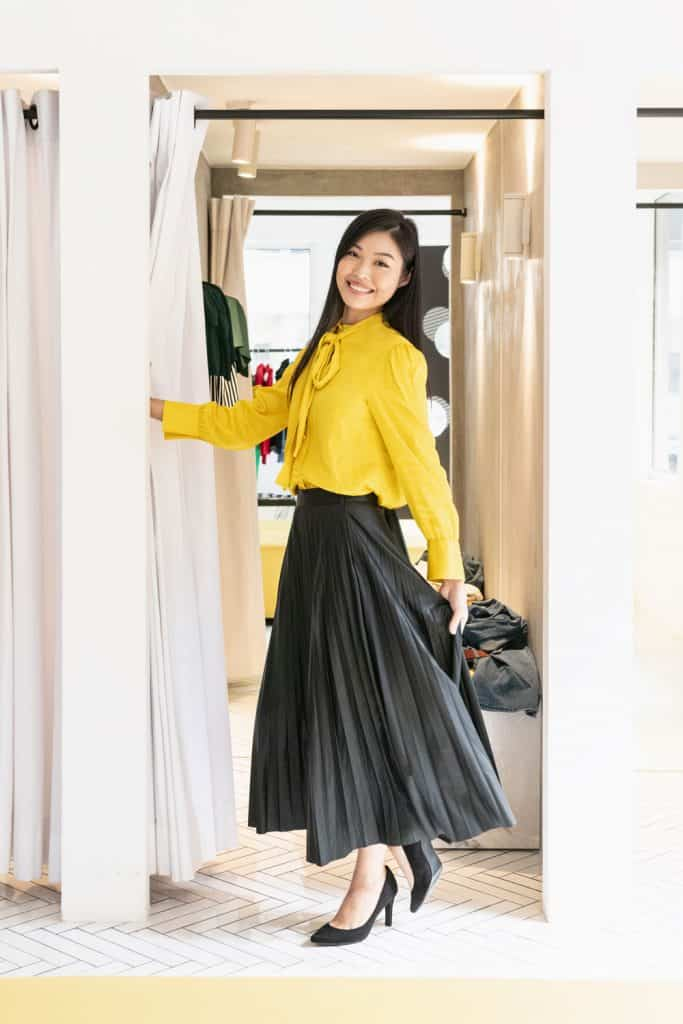 A young woman wearing a yellow blouse and a long black skirt