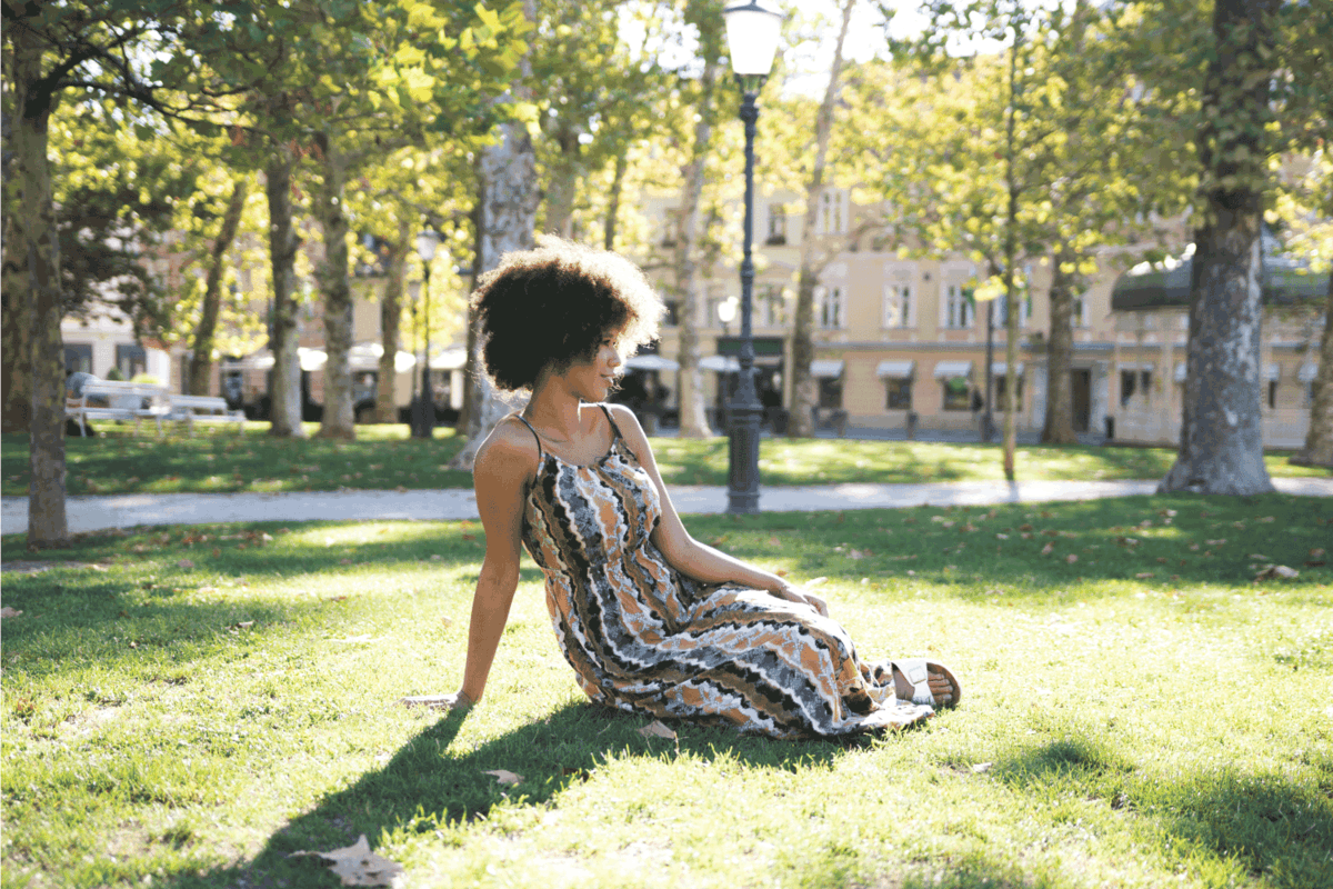 African American woman posing in the park, sitting on the grass