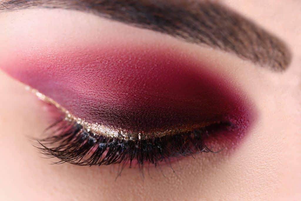An up close photo of a woman's glitter style make up