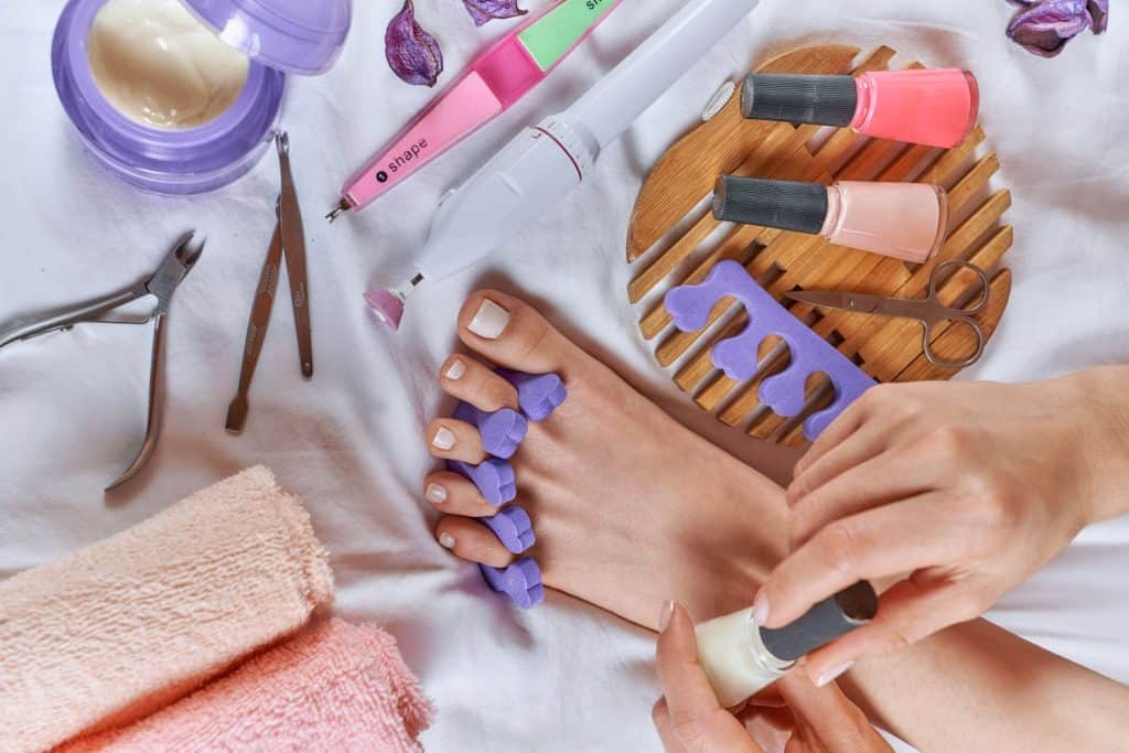 Applying pedicure to woman's feet with white toenails, with toe separators, Does A Pedicure Include Polish?