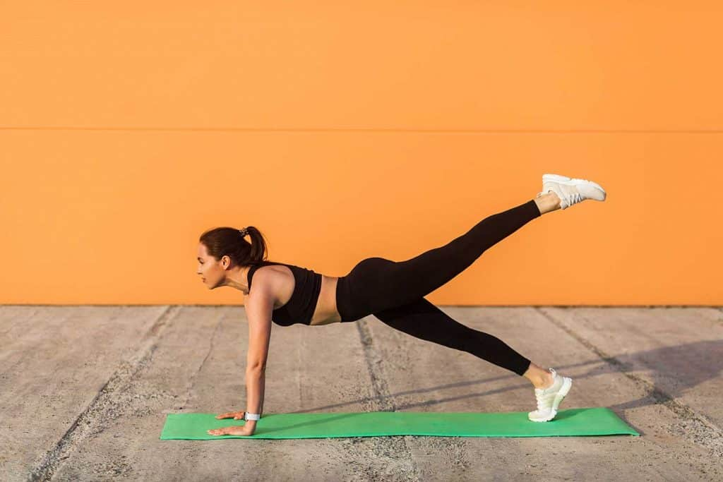 Athletic slim young woman in sportswear, black pants and top practicing yoga
