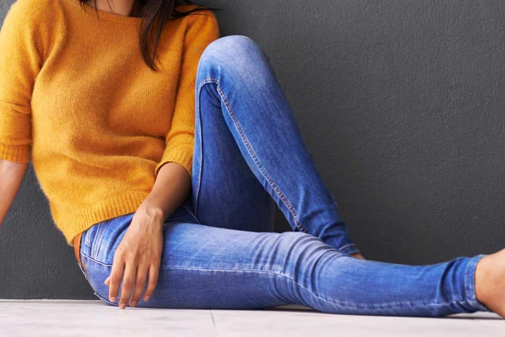 Attractive young woman sitting on the floor wearing jeans, What Tops Go With Skinny Jeans?