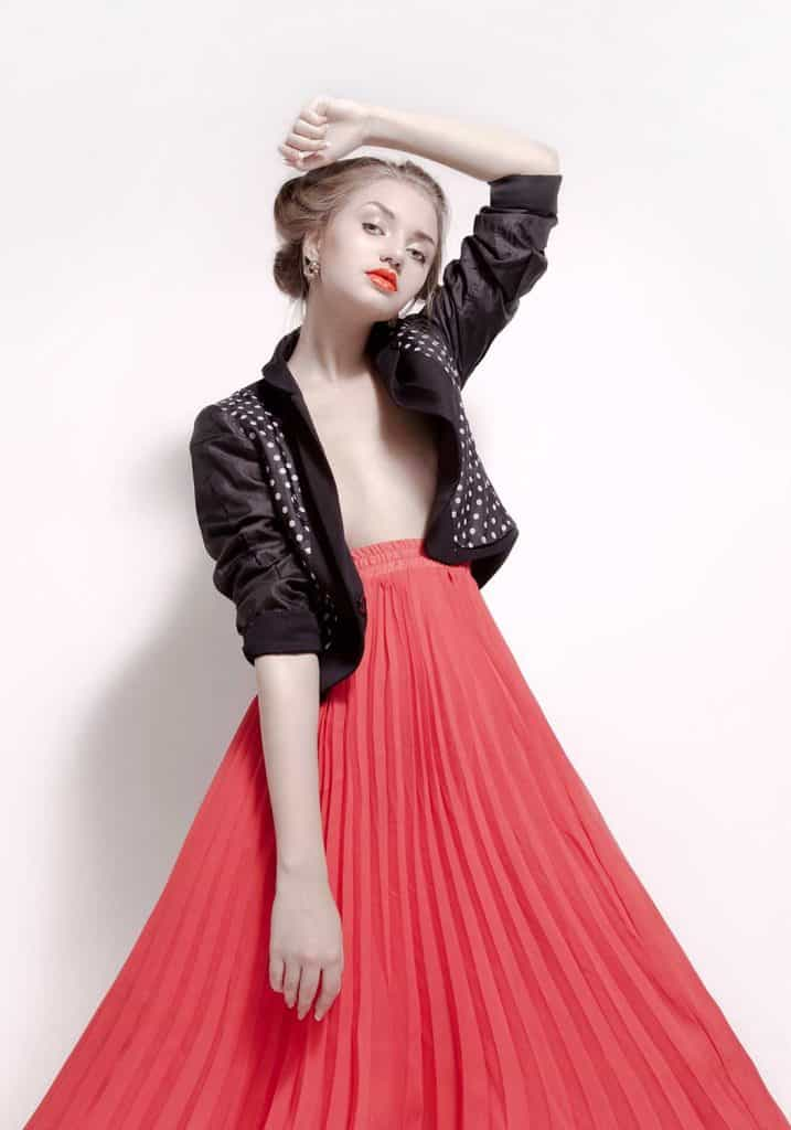 Attractive young woman wearing blazer and pleated skirt