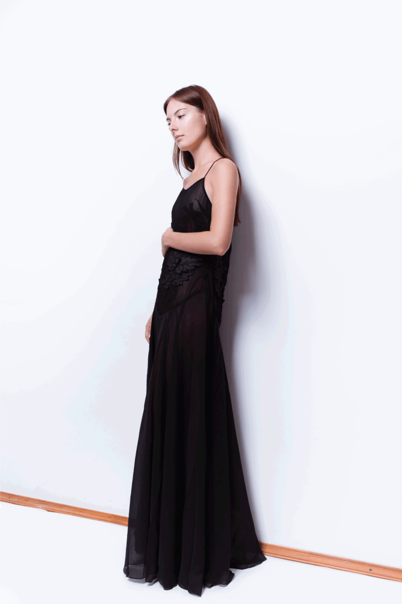 Attractive young woman with natural neutral make-up and simple hairstyle wearing beautiful black long maxi dress