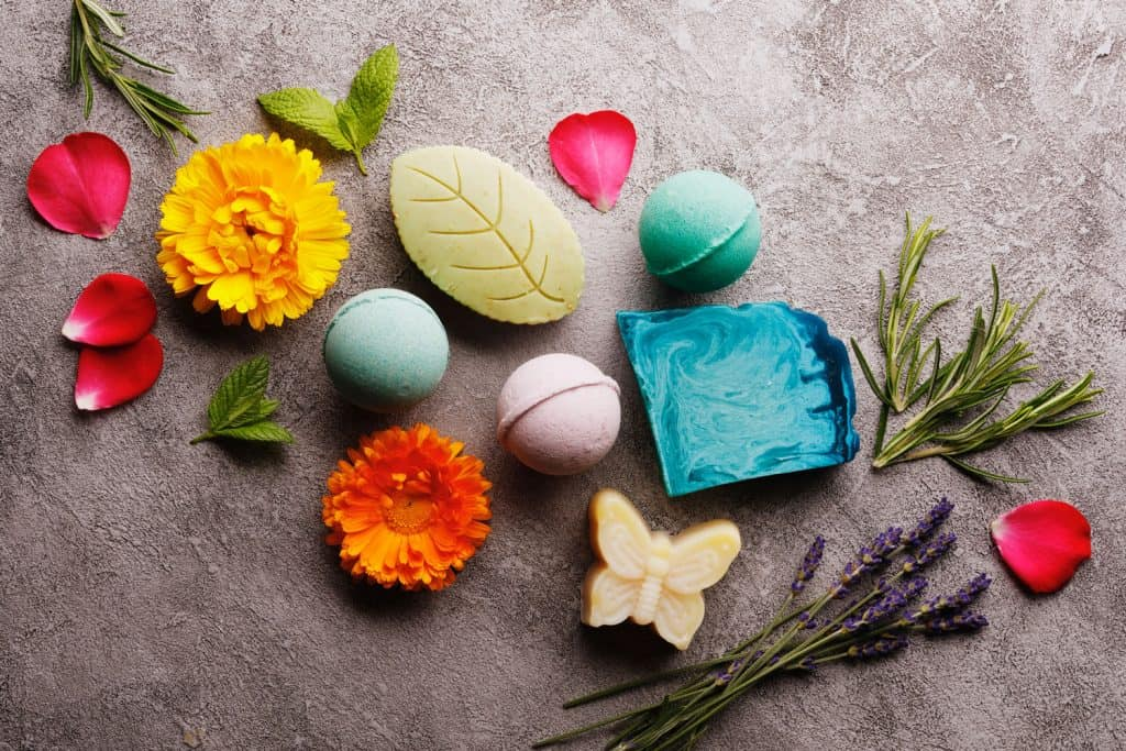 Bath spa accessories on rustic background, colorful bath bombs and soap bars with flowers and herbs, Should You Shower After A Bath Bomb?