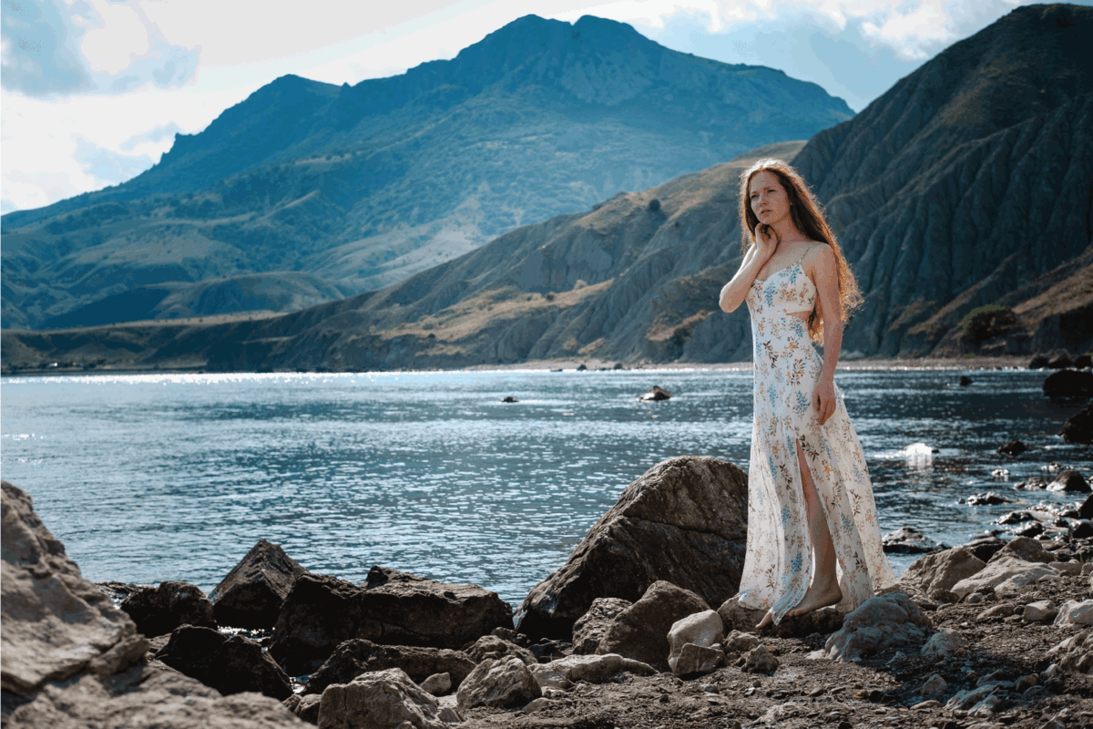 Beautiful boho styled model wearing white dress posing on the beach in sunlight. Red-haired girl