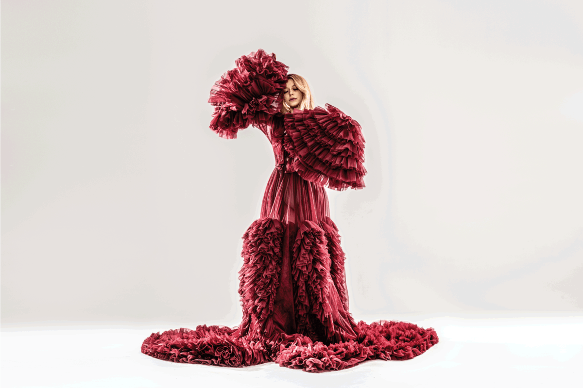 Beautiful elegant blonde woman posing in maroon maxi dress with a lot of ruffles, dancing sensualy, looking like a blooming flower