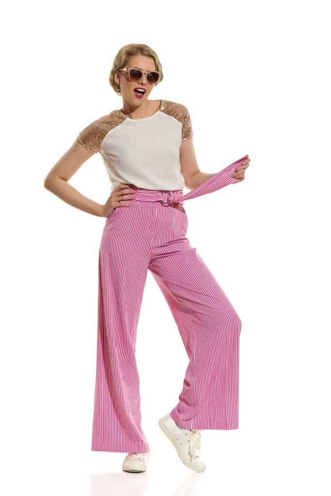 Beautiful young woman is posing in striped wide leg trousers
