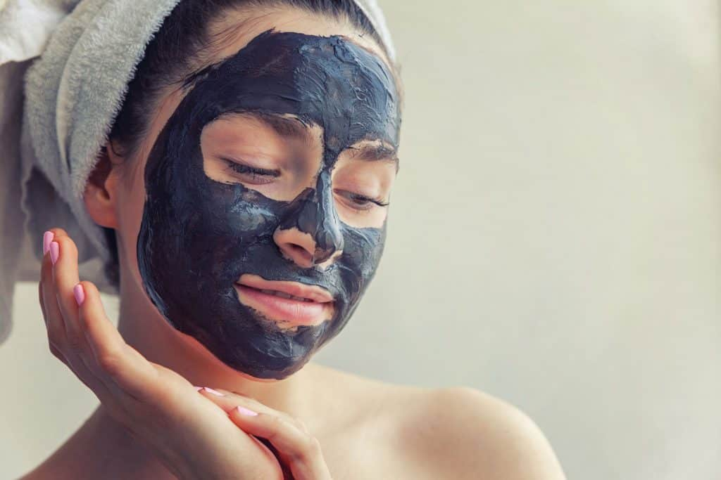 Beauty portrait of woman in towel on head applying black nourishing mask on face, white background isolated