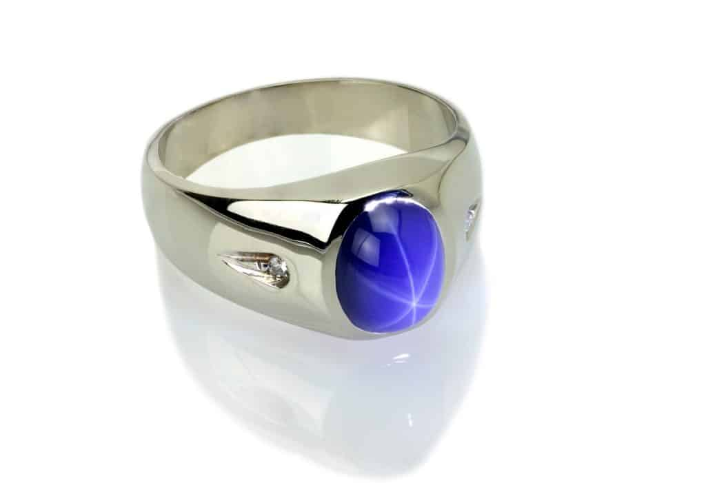 Blue Star Sapphire with Diamond Platinum Ring on White Background.