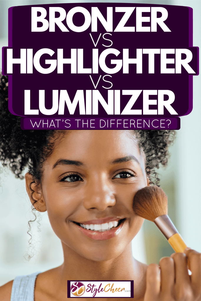 A woman brushing her face with powder inside the powder room, Bronzer Vs Highlighter Vs Luminizer - What's The Difference?