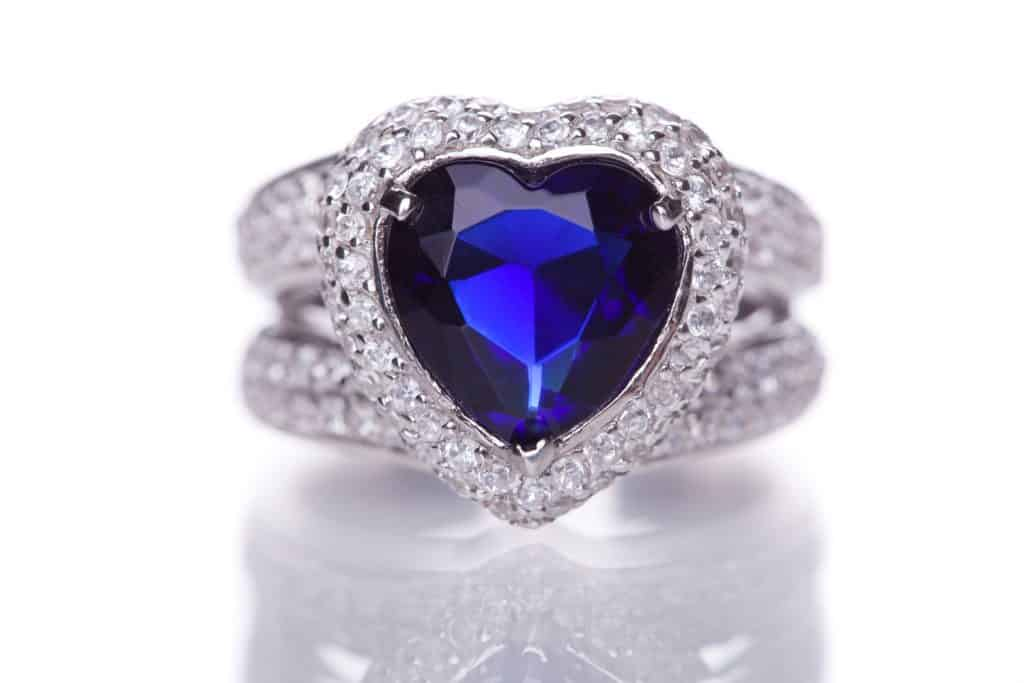 Elegance luxury ring with blue heart shaped sapphire isolated on white background.