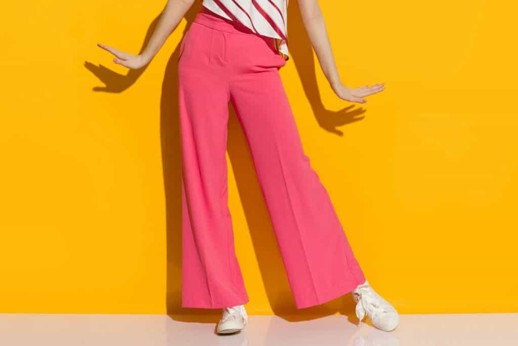 Excited young woman in pink wide leg trousers, How Much Fabric Do You Need For Palazzo Pants?