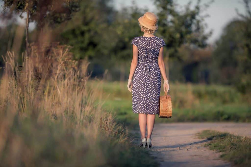 Fashion woman with blue dress and straw hat standing with handbag in rural landscape