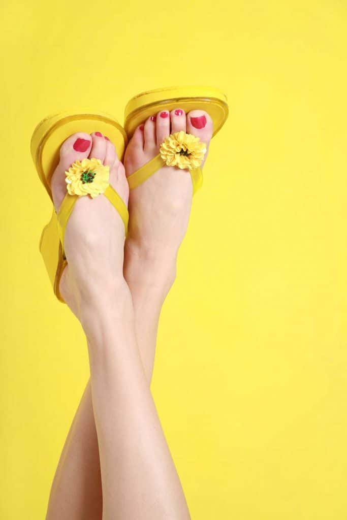 Feet with red nails and yellow flip flops