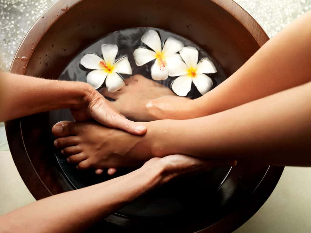 Female feet in foot bath with flowers getting a pedicure