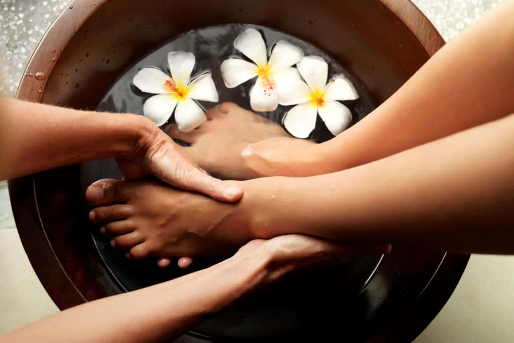 Female feet in foot bath with flowers getting a pedicure, How Much Does A Pedicure Cost? [By Type Of Pedicure]