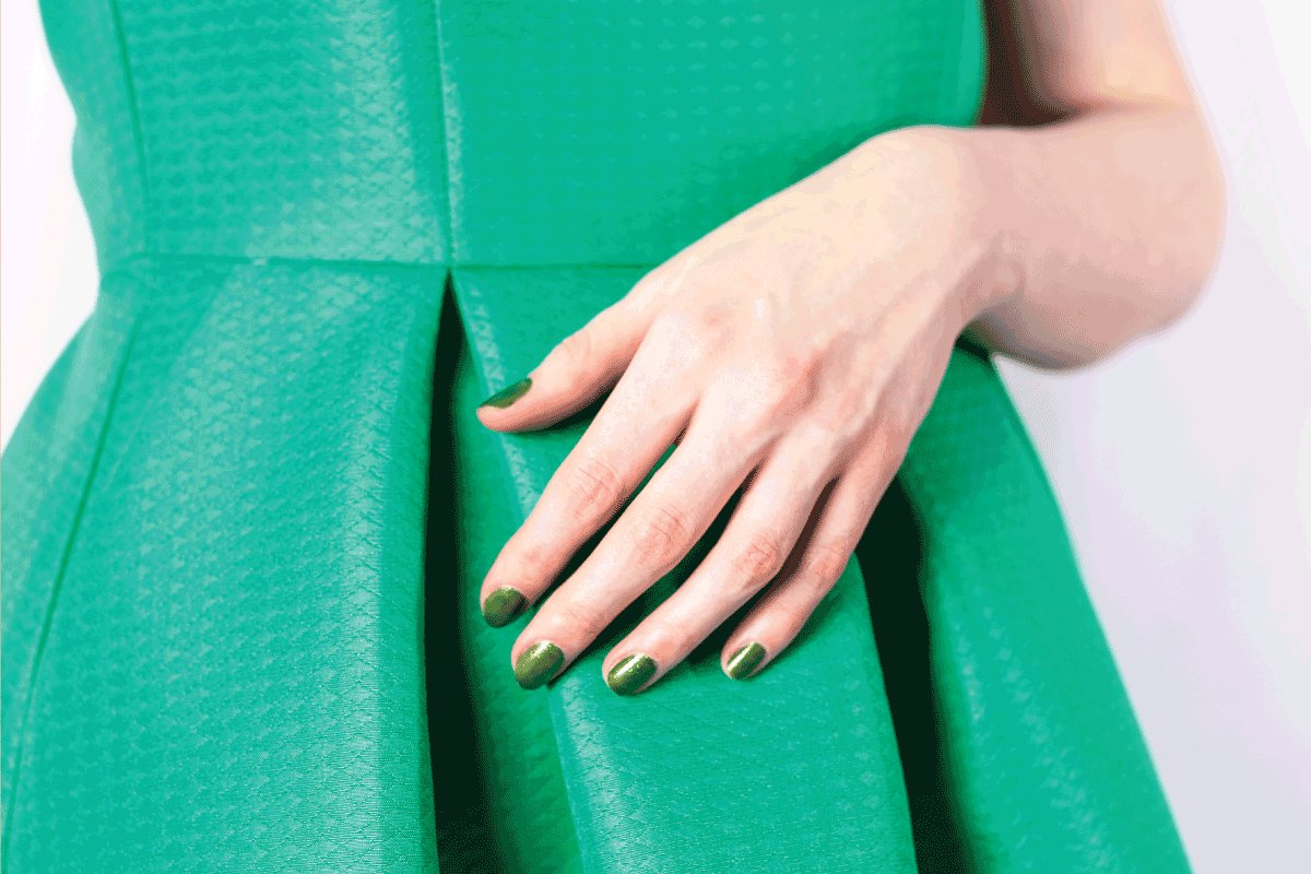 Female hand with green colored nails in green dress. What Color Nails Go With A Green Dress