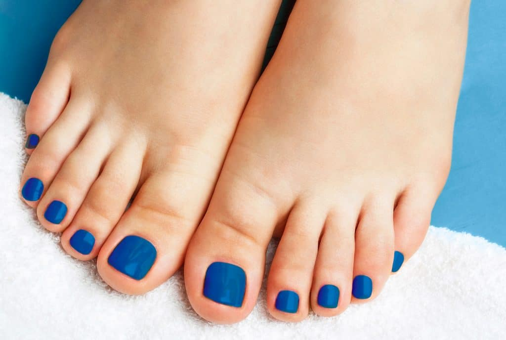 Female legs with pedicure on a white towel close up, concept trend color of the year 2020 Classic Blue.