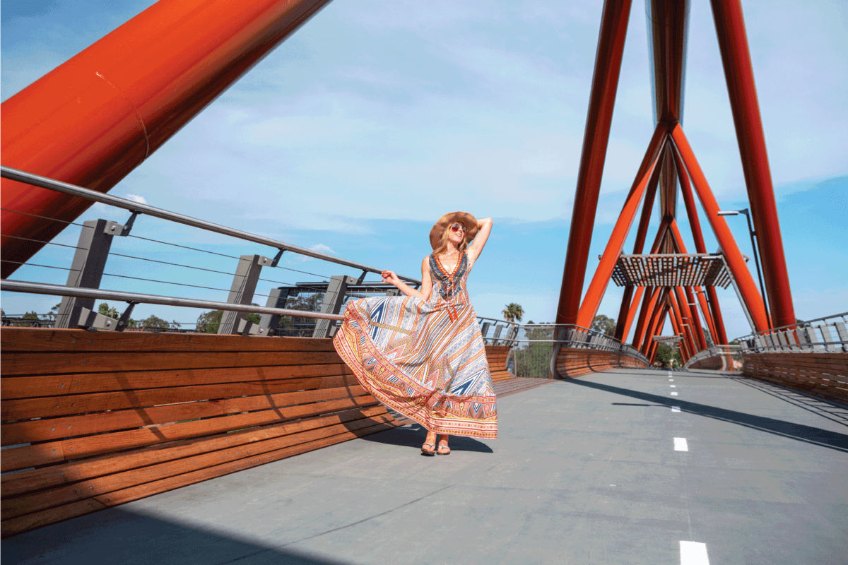 Female wearing a long summer sway dress of vibrant colours and straw hat, walking across the new bridge