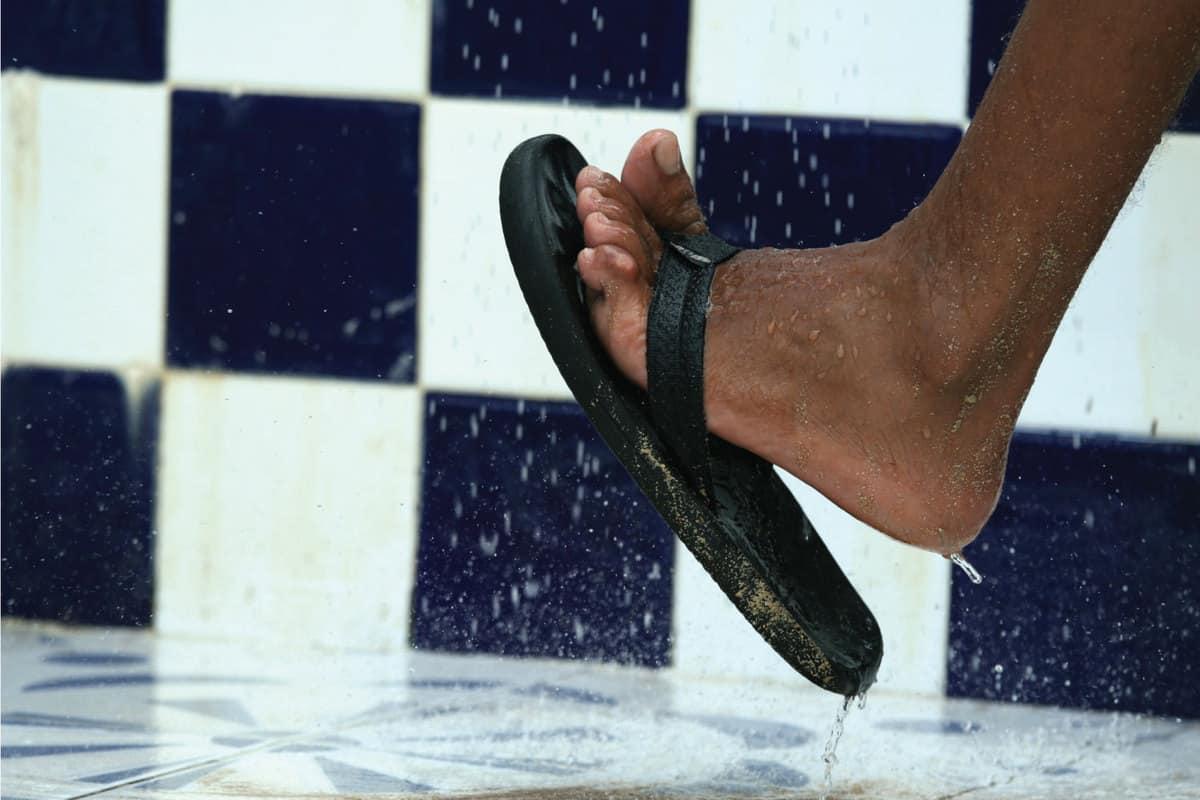 Foot under shower wearing flip flops