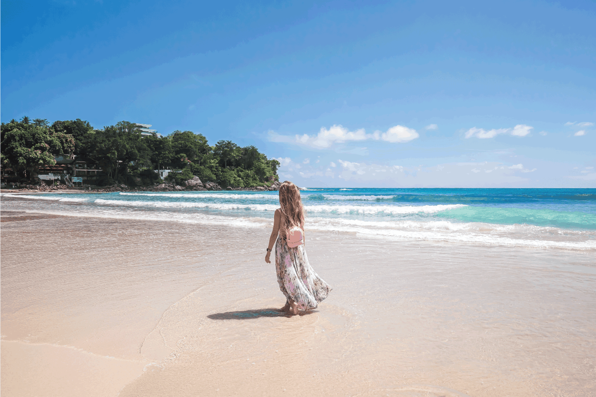 Girl in floral pink maxi skirt walking on the sea shore