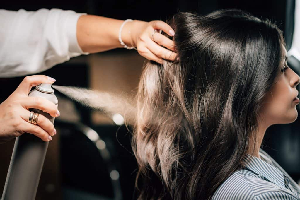 Hairdresser spraying woman's long black hair with hair spray, How Long Does Hairspray Hold?