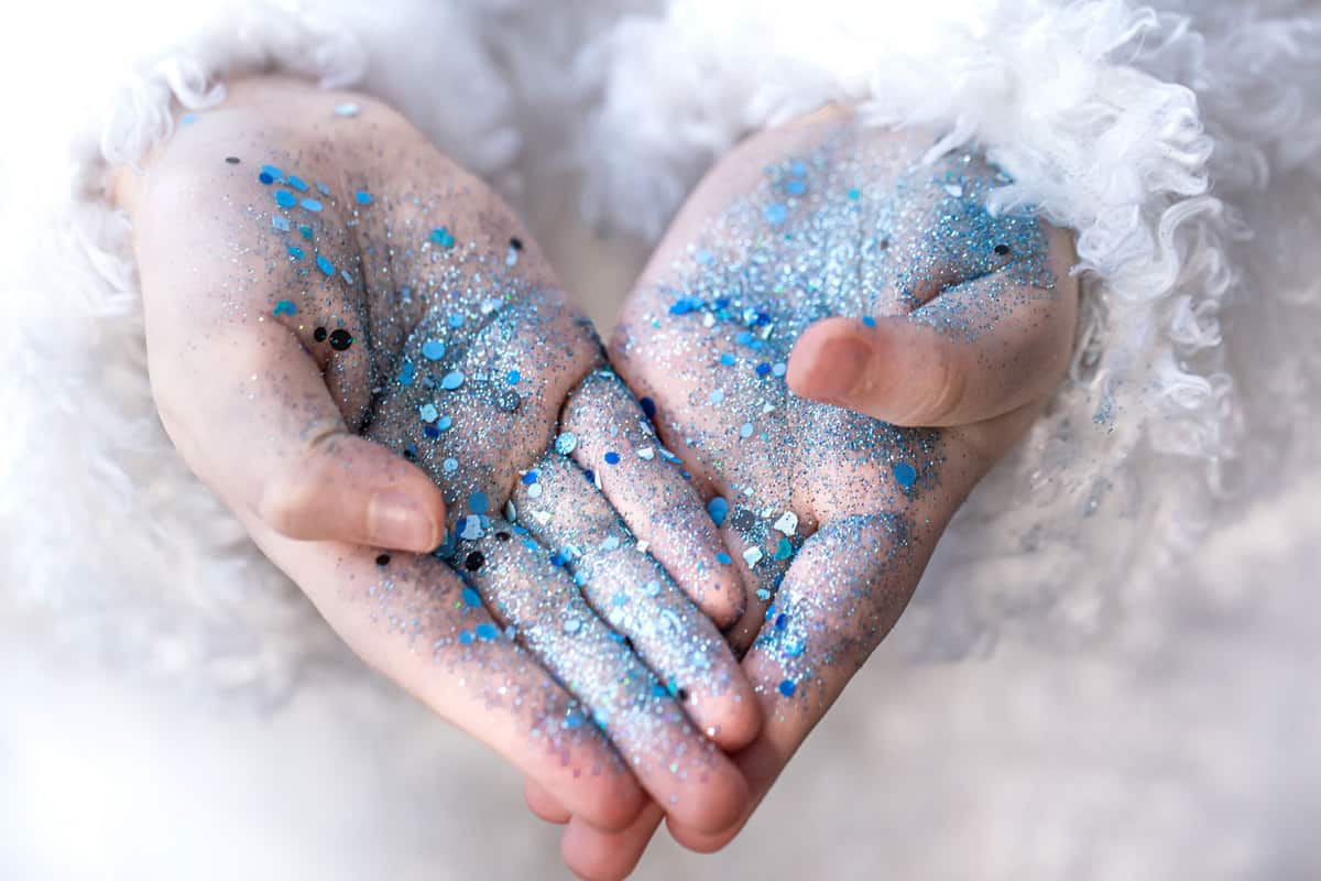 Hands of a little girl in blue sequins, Can You Put Body Glitter In Your Hair?