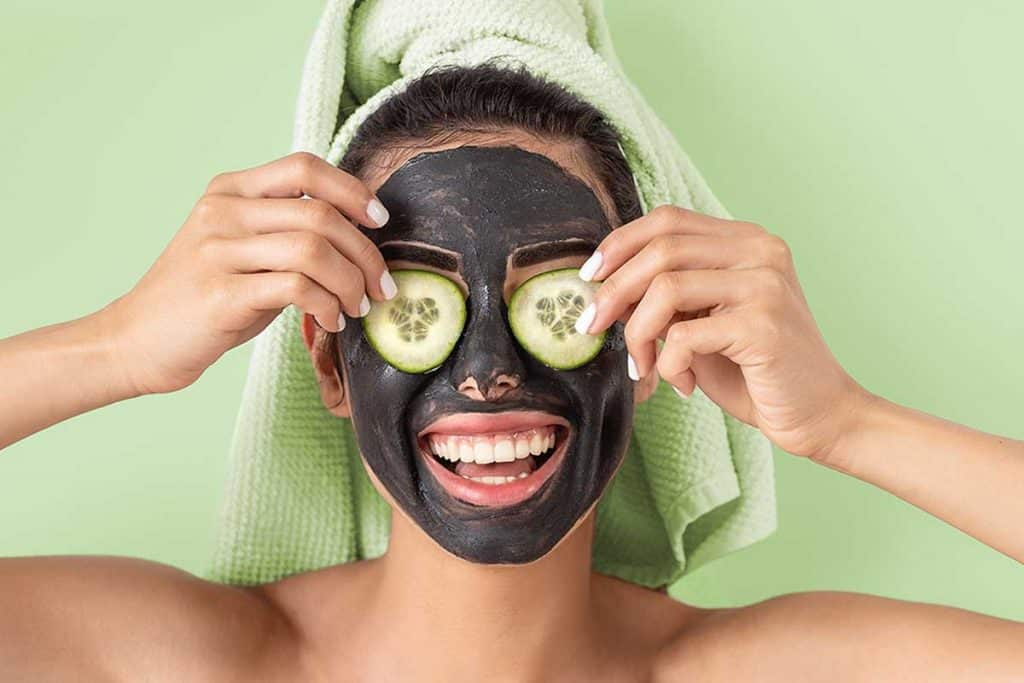 Happy smiling girl applying facial carbon mask, Should You Moisturize After A Charcoal Mask?