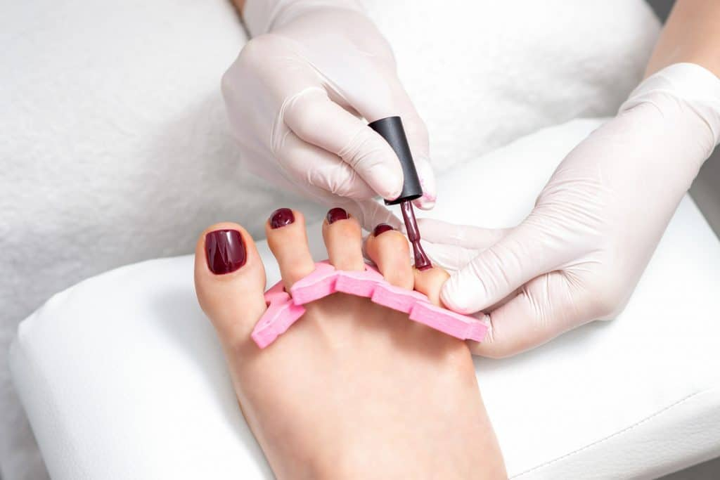 Manicure master is painting on female toenails with maroon nail polish by brush wearing white gloves
