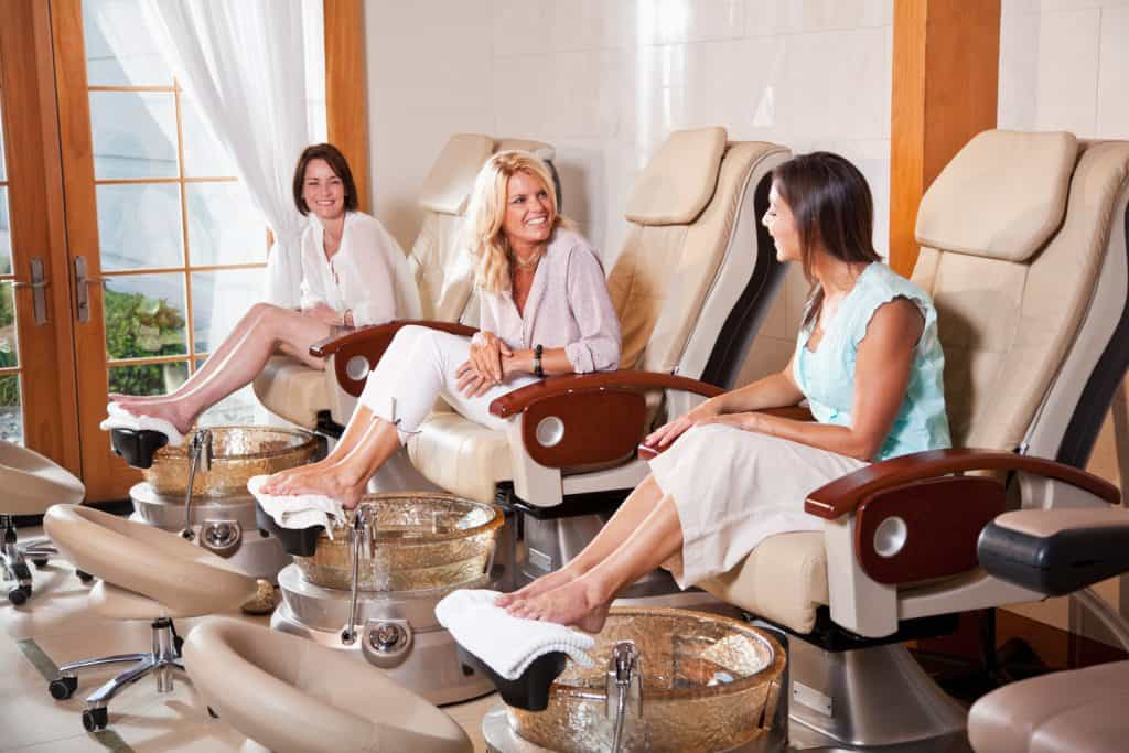 Mature women (40s) at beauty spa getting a pedicures. Main focus on women in foreground talking to each other.