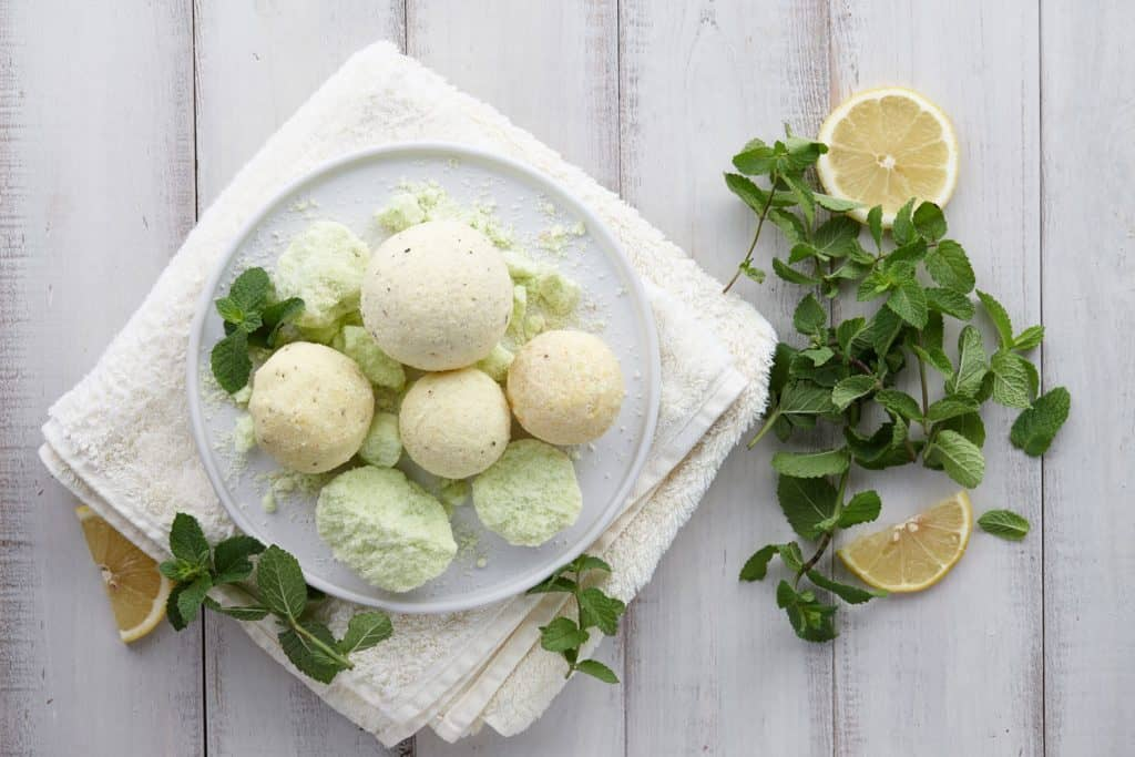 Mint colored bath bomb on a plate with min and lemons on the side