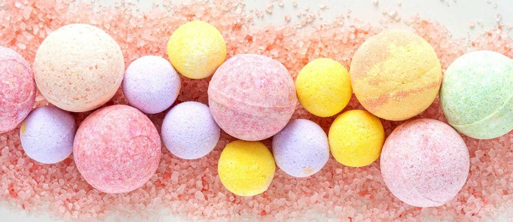 Multicolored bath bombs on pink salt top view