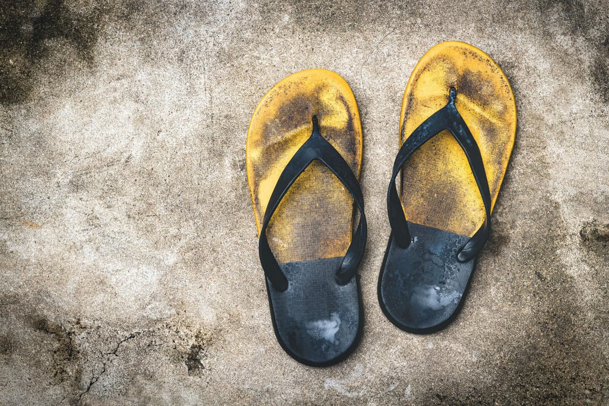 Old and shabby yellow flip-flops lay on the concrete floor.