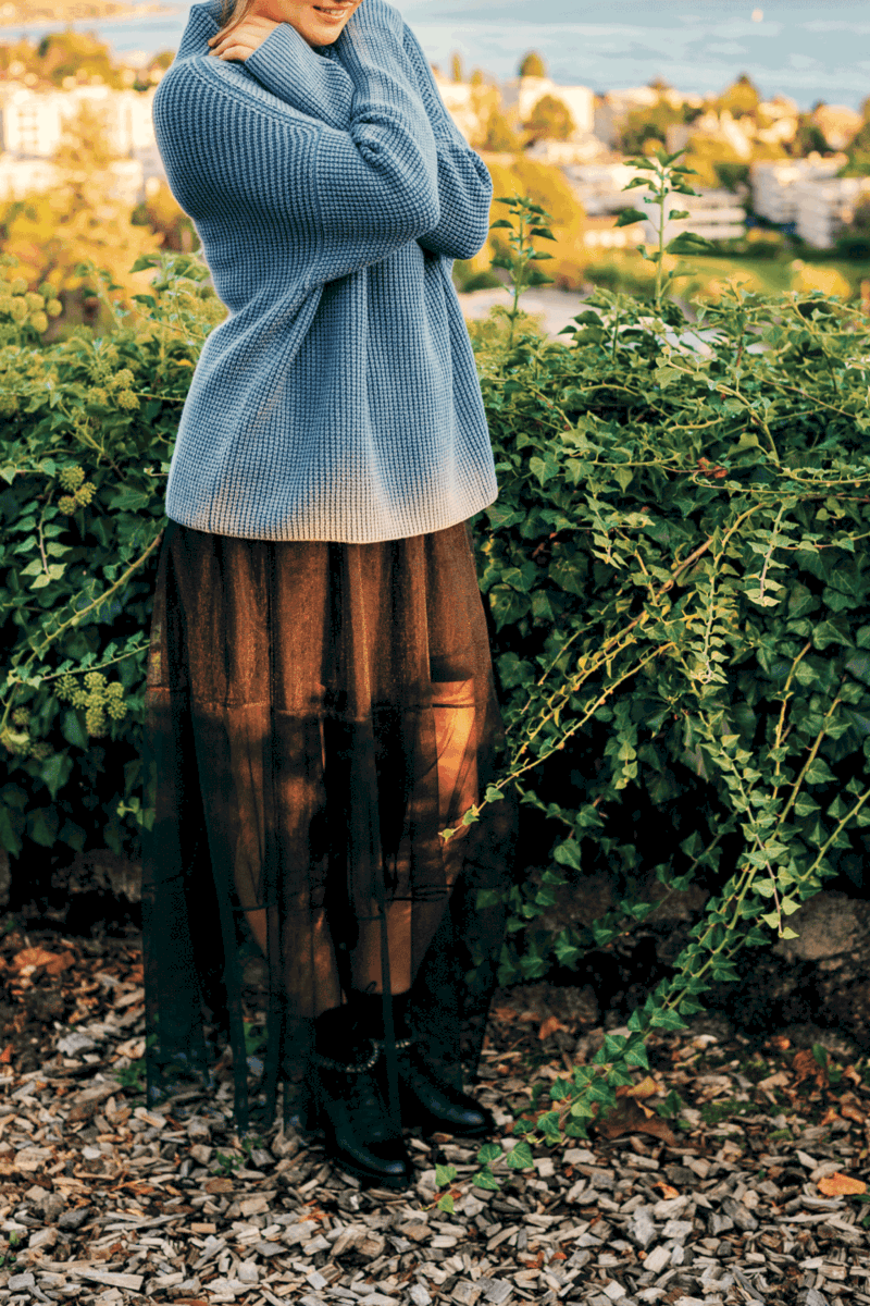Outdoor portrait of beautiful young woman, wearing blue pullover and maxi black skirt