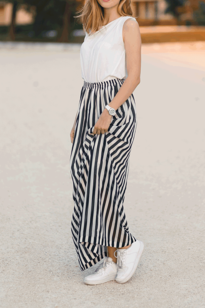 Outdoor portrait of young, beautiful, fashionable smiling girl posing in a stylish, long, feminine striped skirt and white sneakers