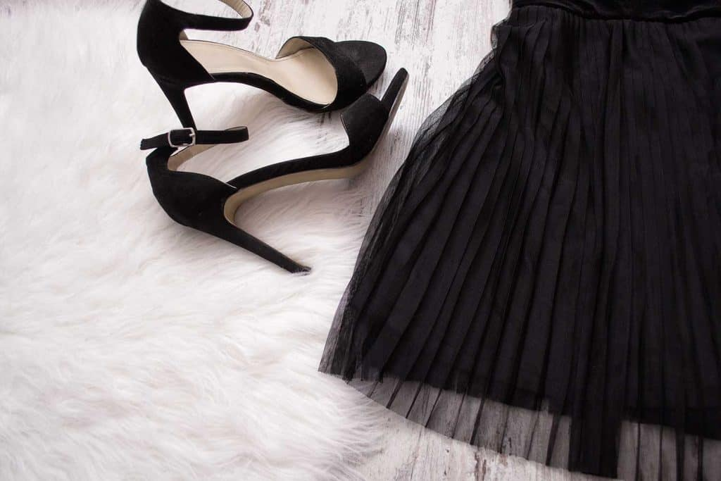Part of a black pleated skirt and black shoes