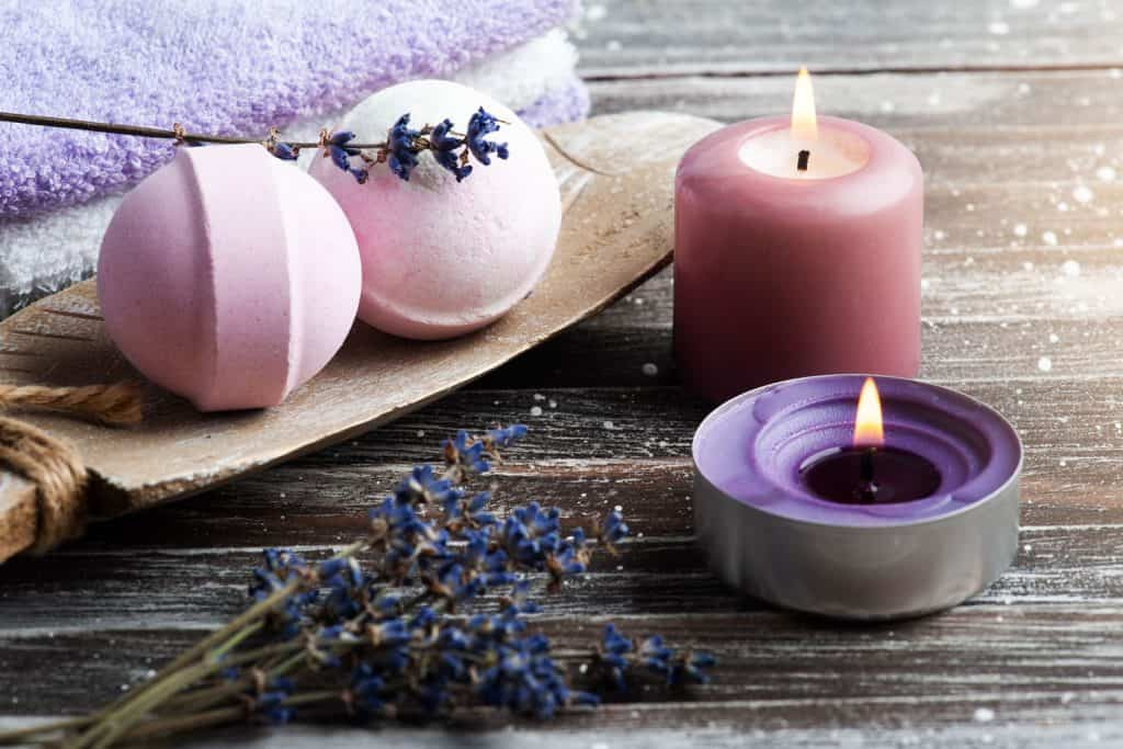 Pink colored bath bombs with a pink candle on the side on top of a wooden table, Can You Use A Bath Bomb In The Shower?