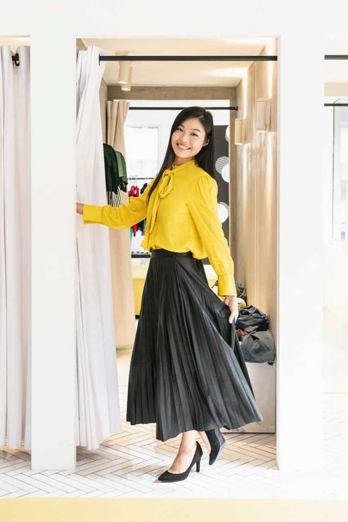 Slim attractive woman wearing full length black skirt and yellow blouse in fitting room