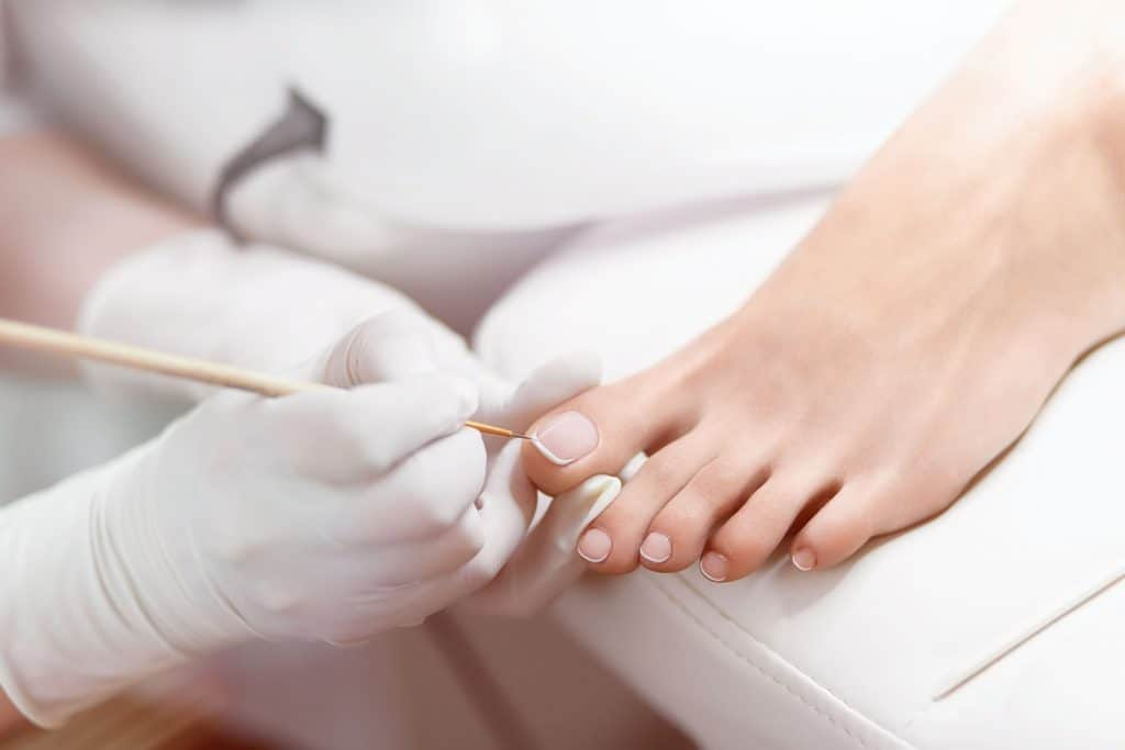 Specialist in beauty salon making french pedicure for female cli