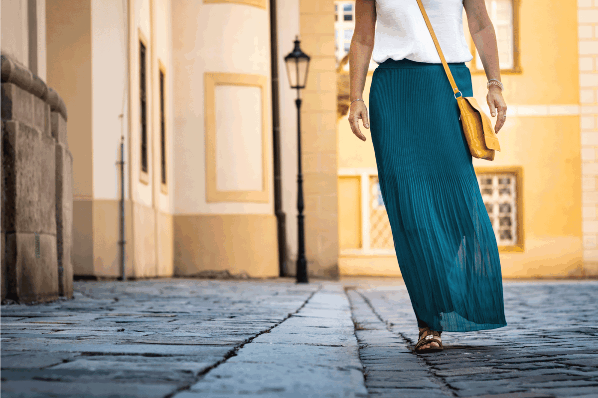 Woman dressed in green pleated skirt is walking at old town