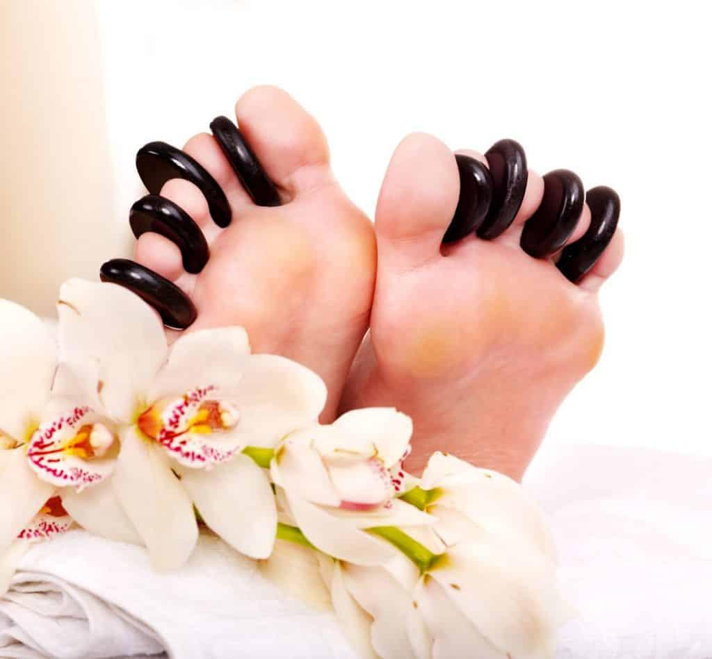 Woman receiving stone massage on feet