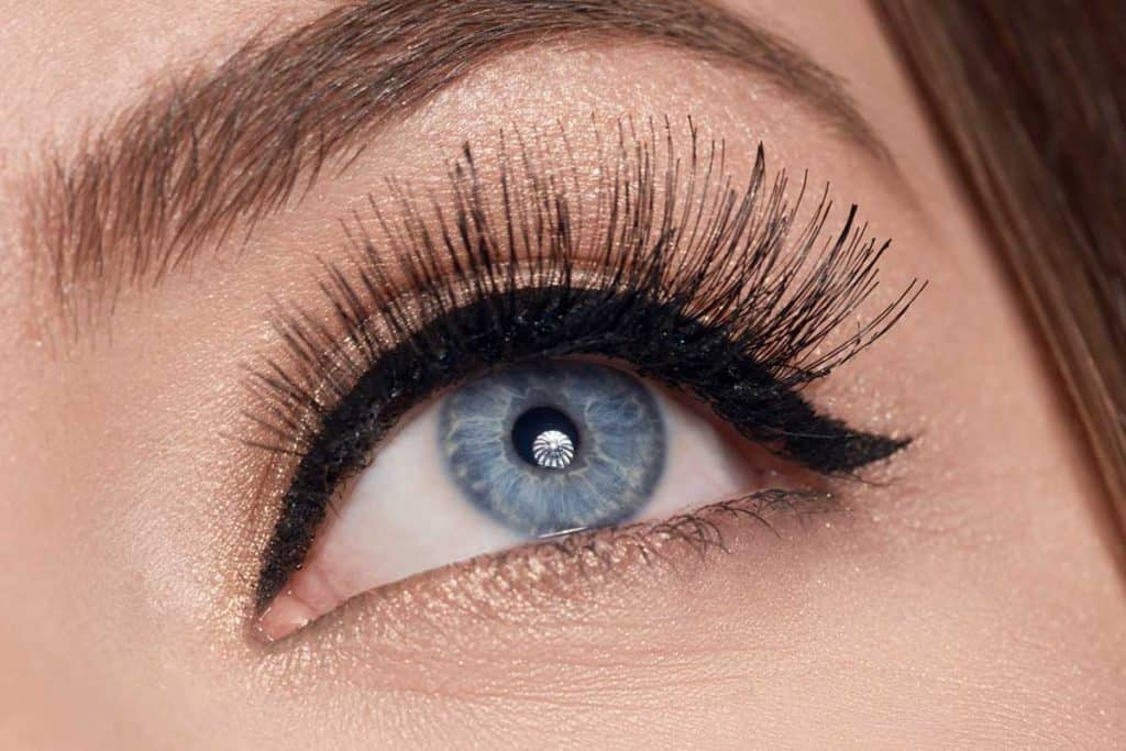 Woman with blue eye and red lips looking away, Should You Apply Eyeliner Before Fake Eyelashes?