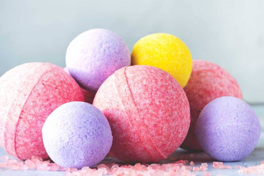 Yellow, pink and purple bath bombs and salt on a gray background, Can A Bath Bomb Dye Your Hair?