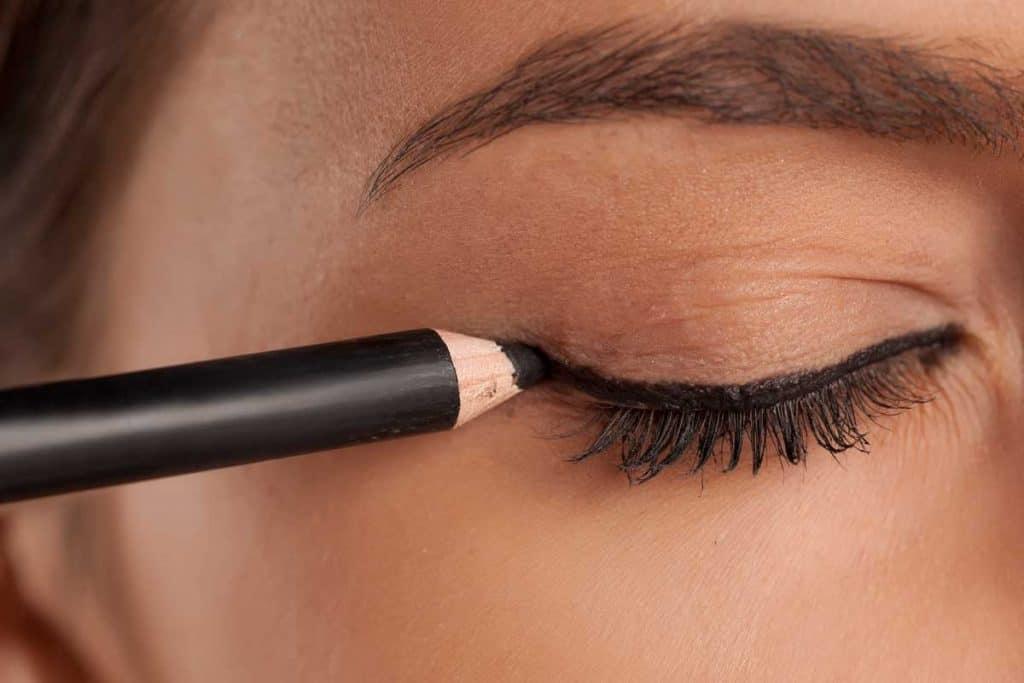 Young woman applying eyeliner makeup, Where Should Eyeliner Start?