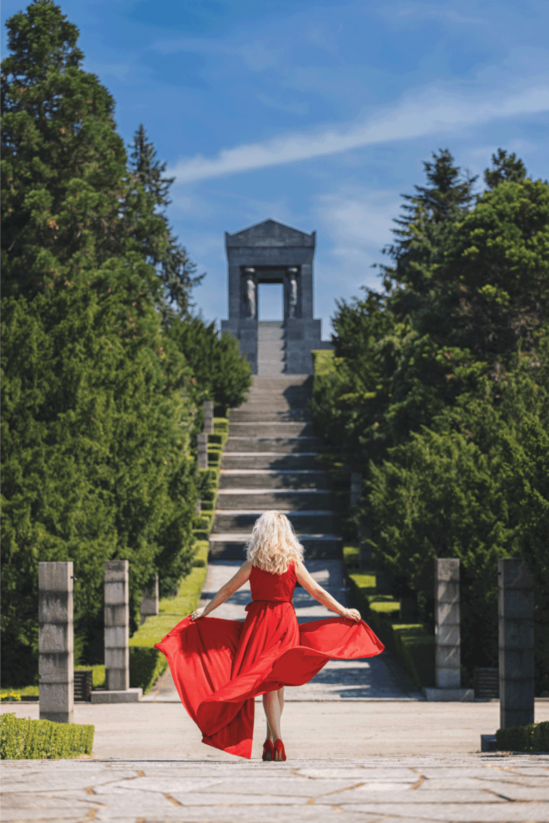 Young woman in long red dress walking on a windy sunny day