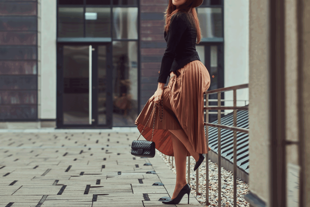 elegant woman wearing a black jacket, brown hat and skirt with a handbag clutch posing while leaning on a steel railing