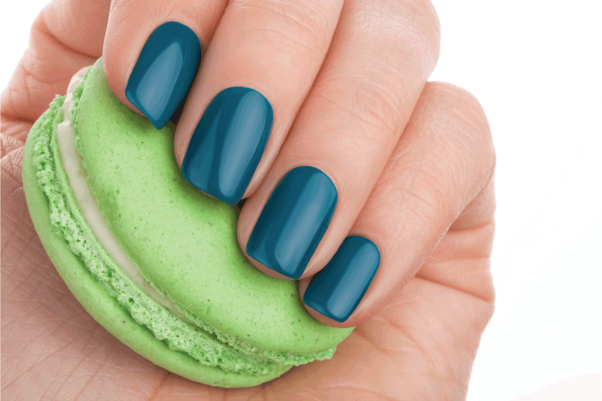 hand wearing green nail polish and holding green macaron