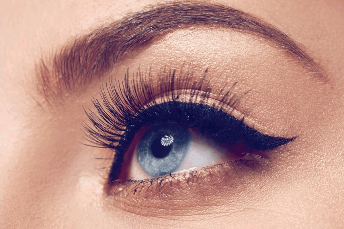 macro shot of woman with blue eye looking away, black eyeliner and mascara.